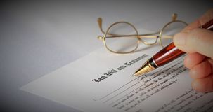 Last Will and Testament. Concept with spectacles and pen document being signed with hand holding pen and copy space stock image