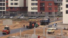Lastbil, asfaltspreader och rullmaskiner Vägpaverarbetare lager videofilmer