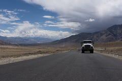 Lastbil som är rörande på en rak väg i ökenslättar av Ladakh Royaltyfri Foto