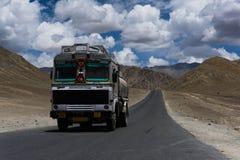 Lastbil som är rörande på en rak väg i ökenslättar av Ladakh Arkivbilder