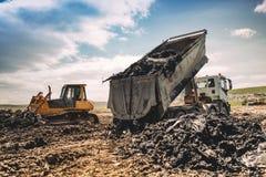 lastbil som lastar av avskräde på att dumpa platsen Industriell bulldozer, grävskopa och dumpa att arbeta för lastbilar Royaltyfri Fotografi