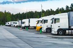 Lastbilar i rad med beh?llare i parkeringsplatsen n?ra skog, logistisk och transportbegrepp arkivfoton