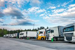 Lastbilar i rad med beh?llare i parkeringsplatsen n?ra skog, logistisk och transportbegrepp royaltyfria bilder