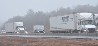 Lastbilar navigerar I-85 nära Greenville SC på dimmig dag Arkivfoto