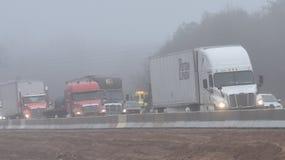 Lastbilar navigerar tilltäppt trafik på I-85 nära Greenville SC på dimmig dag Royaltyfria Foton