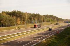 Lastbilar och bilar, medan köra, i bakgrunden ett trafikkontrollsystem och en elektronisk avgiftsamling huvudväg arkivbild