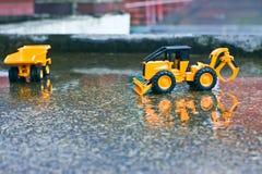 Lastbilar och folkleneleksaker på cementgolv efter vårregn royaltyfria bilder
