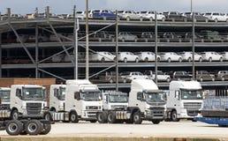 Lastbilar och lyxbilar väntar på exporten från skeppsdockor UK royaltyfri fotografi