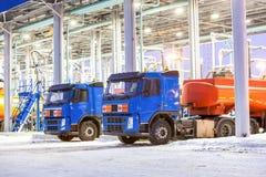 Lastbilar på bensinstationen på oljeraffinaderifabrik Arkivfoto