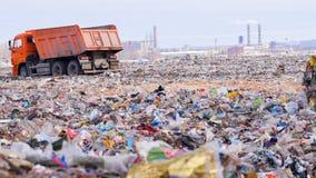 Lastbilar på en enorm nedgrävning av sopor
