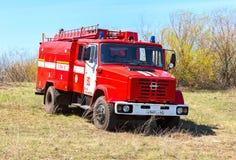 Lastbilen för röd brand EMERCOM av Ryssland parkerade upp på vårfältet Royaltyfri Fotografi