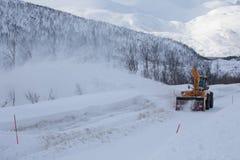 Lastbilen för snöplogen som gör klar den iskalla vägen efter vintersnöstormhäftiga snöstormen för blåsare för medeltill arkivbilder