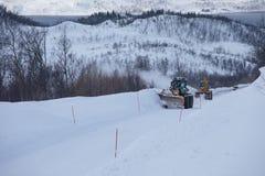 Lastbilen för snöplogen som gör klar den iskalla vägen efter vintersnöstormhäftiga snöstormen för blåsare för medeltill arkivfoton
