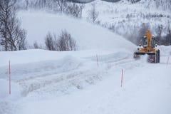 Lastbilen för snöplogen som gör klar den iskalla vägen efter vintersnöstormhäftiga snöstormen för blåsare för medeltill fotografering för bildbyråer