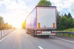 Lastbilen går på huvudvägen till soluppgång Royaltyfri Bild