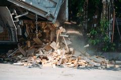 Lastbilen häller ut trät på jordningen Arkivbild