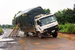 Lastbilen har proplem med mycket krukahål på highway.en BINH PHUOC, VIETNAM SEPTEMBER 1 Arkivfoton