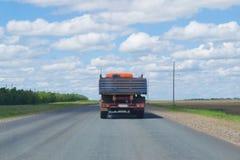 Lastbilen kör på huvudvägen under den blåa himlen arkivbild