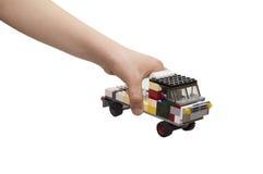 Lastbilen som göras från byggnadssats i ett barns hand arkivfoto