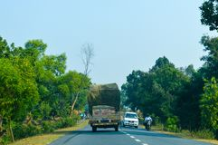 Lastbilen transporterar gods vid vägen - sändnings och logistiken royaltyfria bilder