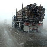 Lastbillastbilstransporten loggar in vinterstormen Arkivfoton