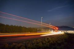 Lastbilljusslingor i tunnel Långt exponeringsfoto som tas i en tunnel Långt exponeringsfoto som tas på en väg bredvid sjösidan royaltyfri bild
