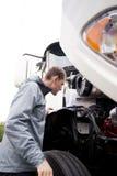 Lastbilsförare som kontrollerar den halva lastbilmotorn för vit stor rigg Royaltyfri Foto
