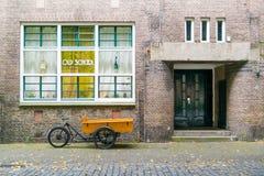 Lastcykeln parkerade framme av skolan, Leiden, Nederländerna Royaltyfri Bild