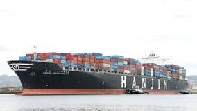 Lastfartyg HANJIN FÖRENADE KUNGARIKET som avgår porten av Oakland Arkivbild
