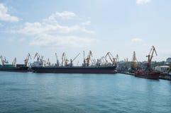 Lastfartyg och kranar i hamnstaden Royaltyfri Fotografi