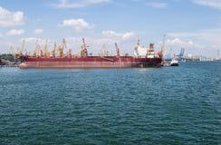 Lastfartyg och kranar i hamnstaden Arkivfoton