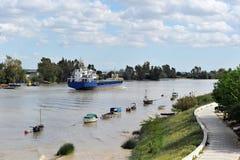 Lastfartyg på floden Guadalquivir i dess passage till och med Coria del RÃo, Sevilla, AndalucÃa, Spanien arkivfoto