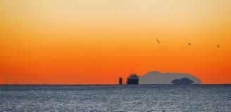 Lastfartyg på sunrising arkivbild
