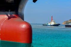 Lastfartyg som förtöjas och förtöjas pollaren med ett fast rep på framdelen av den lökformiga pilbågeskepplogistiken och trans. arkivfoto