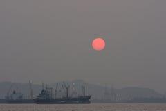Lastfartyg som svävar i havet medan solnedgången, kontursolnedgång Royaltyfri Bild