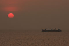 Lastfartyg som svävar i havet medan solnedgången, kontursolnedgång Royaltyfri Fotografi