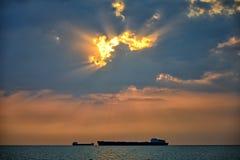 Lastfartyg som svävar på en bakgrund av en härlig solnedgång Arkivfoto