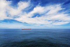 Lastfartyg under blå himmel i havet Fotografering för Bildbyråer