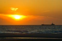 Lastfartyget går tillbaka till port under solnedgång royaltyfria foton