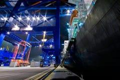 Lastfartygpäfyllningsbehållare vid natt Arkivfoto