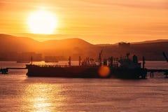 Lastfraktskepp i hamn i den dramatiskt den logistiska solnedgångsikten, vattentrans. och skytteln royaltyfri foto