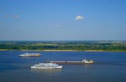 Lastkahn und Schiffe, die auf die Wolga segeln Panoramablicke über der Ebene, die mit dem Himmel auf dem Horizont verschmilzt Stockfotografie