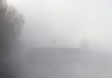 Lastkahnlieferung im starken Nebel Stockfotos