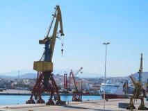 Lastkranar och skepp i havsporten över blå himmel Arkivbild