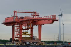 Lastningsbrygga Crane Loading Container på lastbilen med vindturbinen i bakgrund Royaltyfri Bild