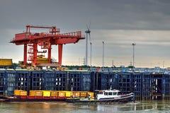 Lastningsbryggan Crane Loading Container på lastbilen med bogserbåten och rusar in förgrund Fotografering för Bildbyråer
