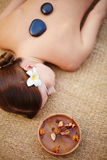 During lastone therapy. Lying woman during lastone massage stock photo
