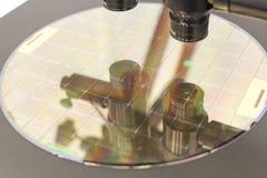 Lastra di silicio sul processo della macchina che esamina in microscopio fotografia stock