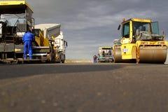 Lastricatori seguiti che pongono la pavimentazione fresca dell'asfalto su una pista come componente del piano di espansione dell' Immagini Stock