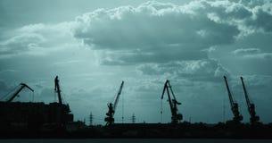 Lastskepp-lyftande kranar på floden i den tonade porten Royaltyfria Bilder